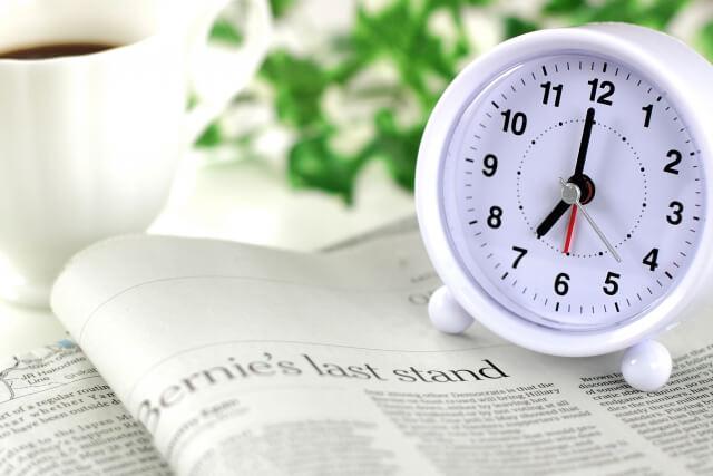 朝の風景。目覚まし時計と新聞