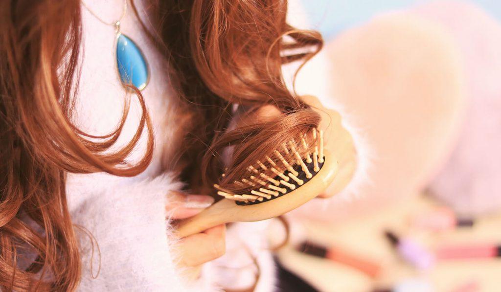 髪の毛をヘアブラシでとかす女性