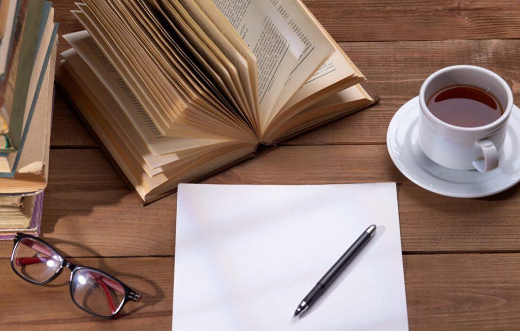 本とコーヒー。ノートとメガネとシャープペンシル