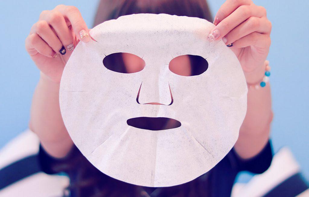 フェイスマスクシートを持つ女性